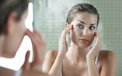Woman examining face in mirror