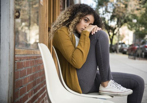 Pensive Mixed Race woman sitting on chair in city