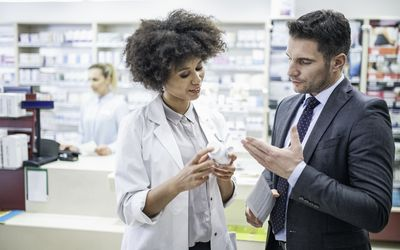 Pharmacist advising man on the benefits of a drug