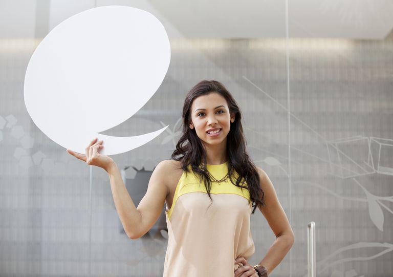 Woman holding blank speech bubble.