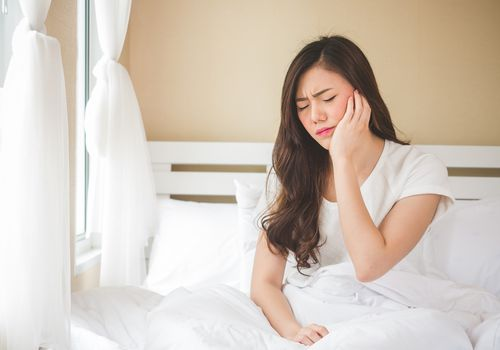 Woman in bed with hand on her face in pain