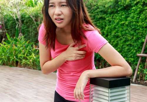 Young woman having heart attack