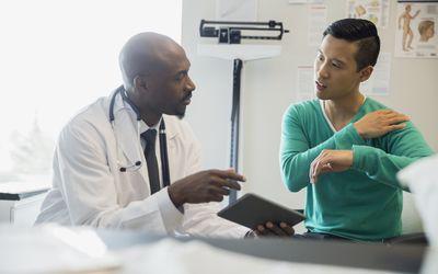 Patient explaining shoulder pain to doctor