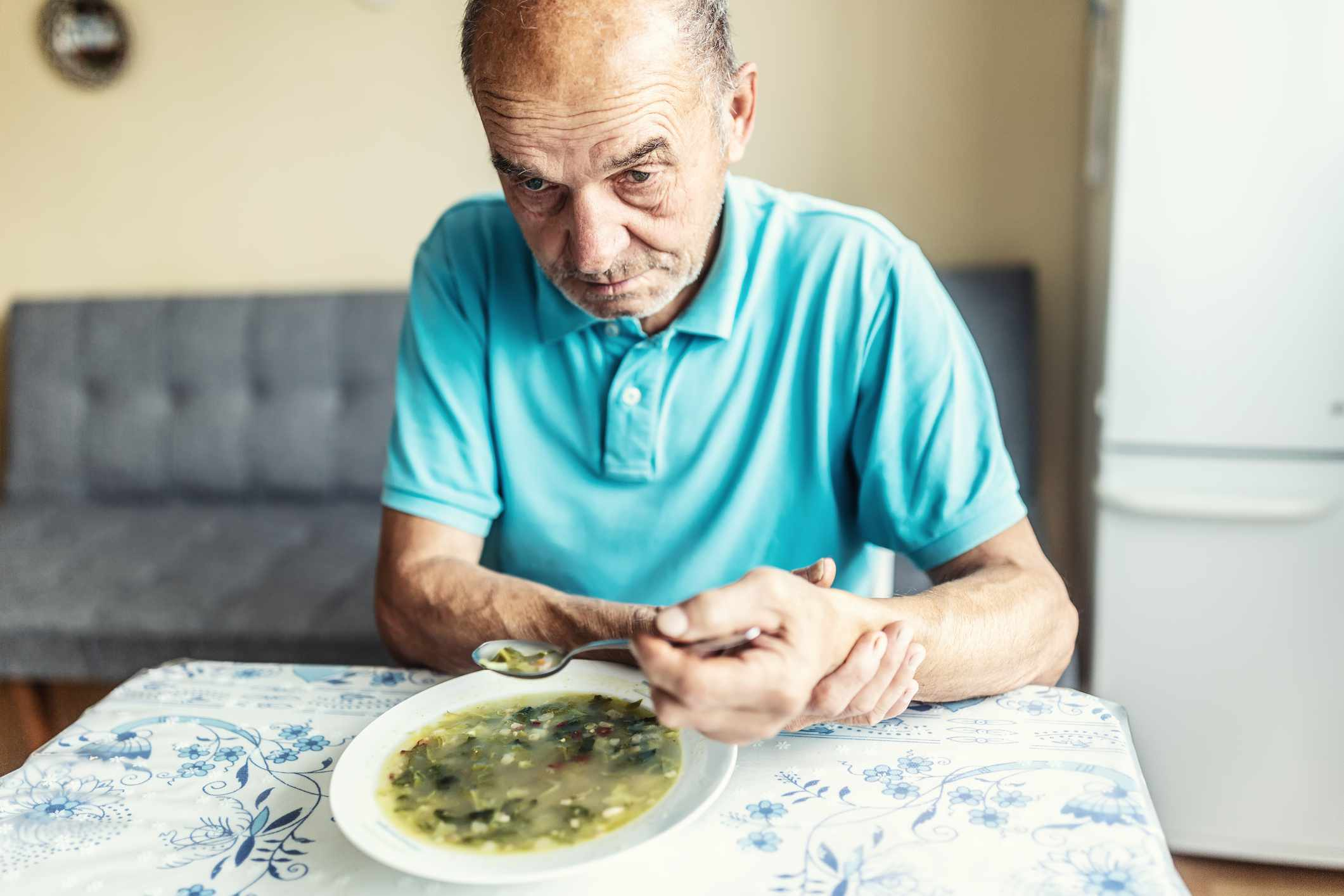 A senior man with Parkinson's disease holds his arm with a hand, trying to eat a soup