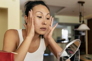 Woman pulling back skin on face and looking in the mirror