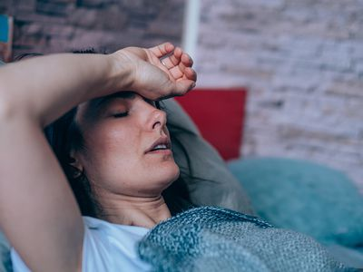 Woman looking feverish in bed