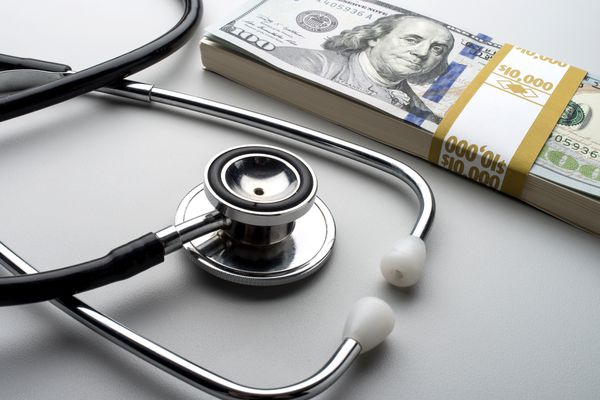 Stethoscope and money on table