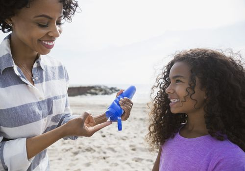 Mother applying sunscreen to daughter on beach
