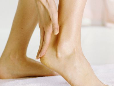 Young woman applying lotion to foot, close-up, low section