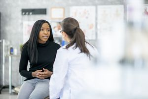 A woman is holding her abdomen while consulting with a medical professional.