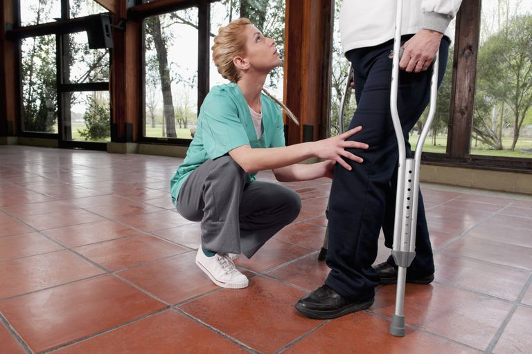 Man using crutches while physical therapist looks at knee