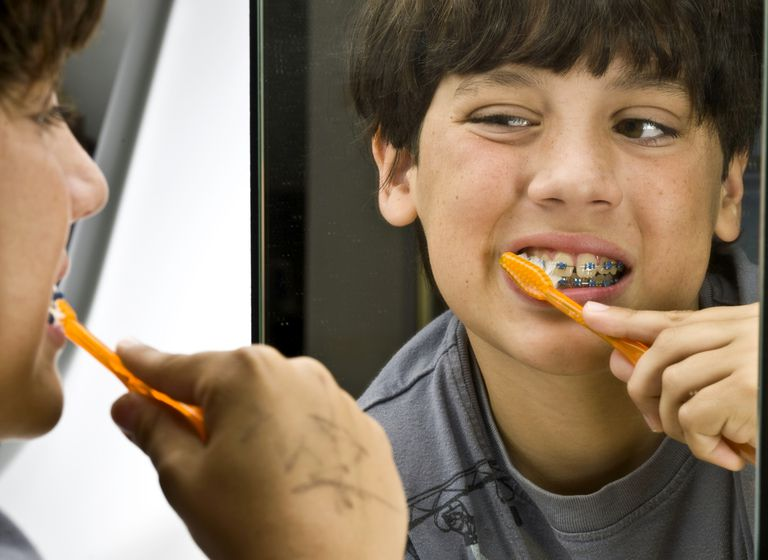 boy with braces brushing teeth