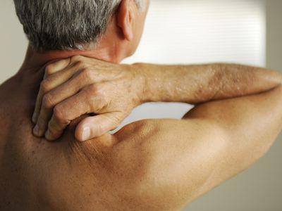 Man rubbing neck in pain