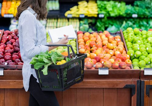 Young woman carries a shopping basket filled with fresh produce