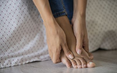 Low section of young woman massaging her foot.