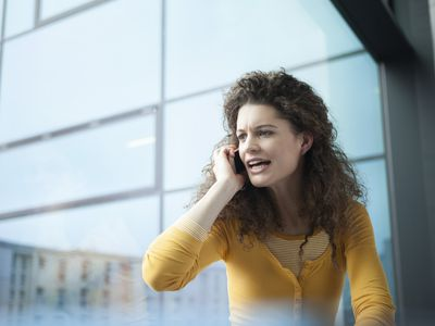 Angry young woman on the phone at the window