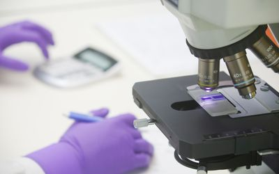microscope in foreground with scientist's gloved hands in background