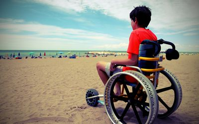 Young boy with t-shirt sitting on the special wheelchair with aluminum alloy wheels with vintage effect in summer
