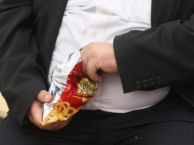 An obese man eats junk food.