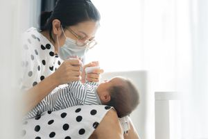 Small infant in mother's lap as she wears a face mask.