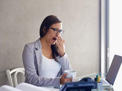 Woman yawning at work.