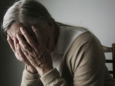 elderly woman with hands covering face