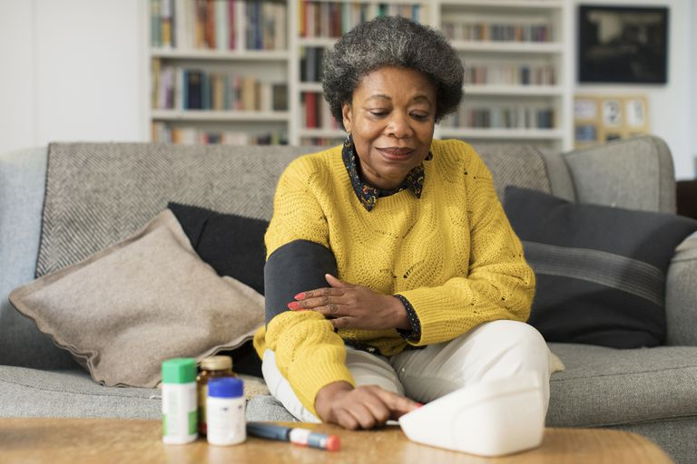 Black woman checking her blood pressure at home