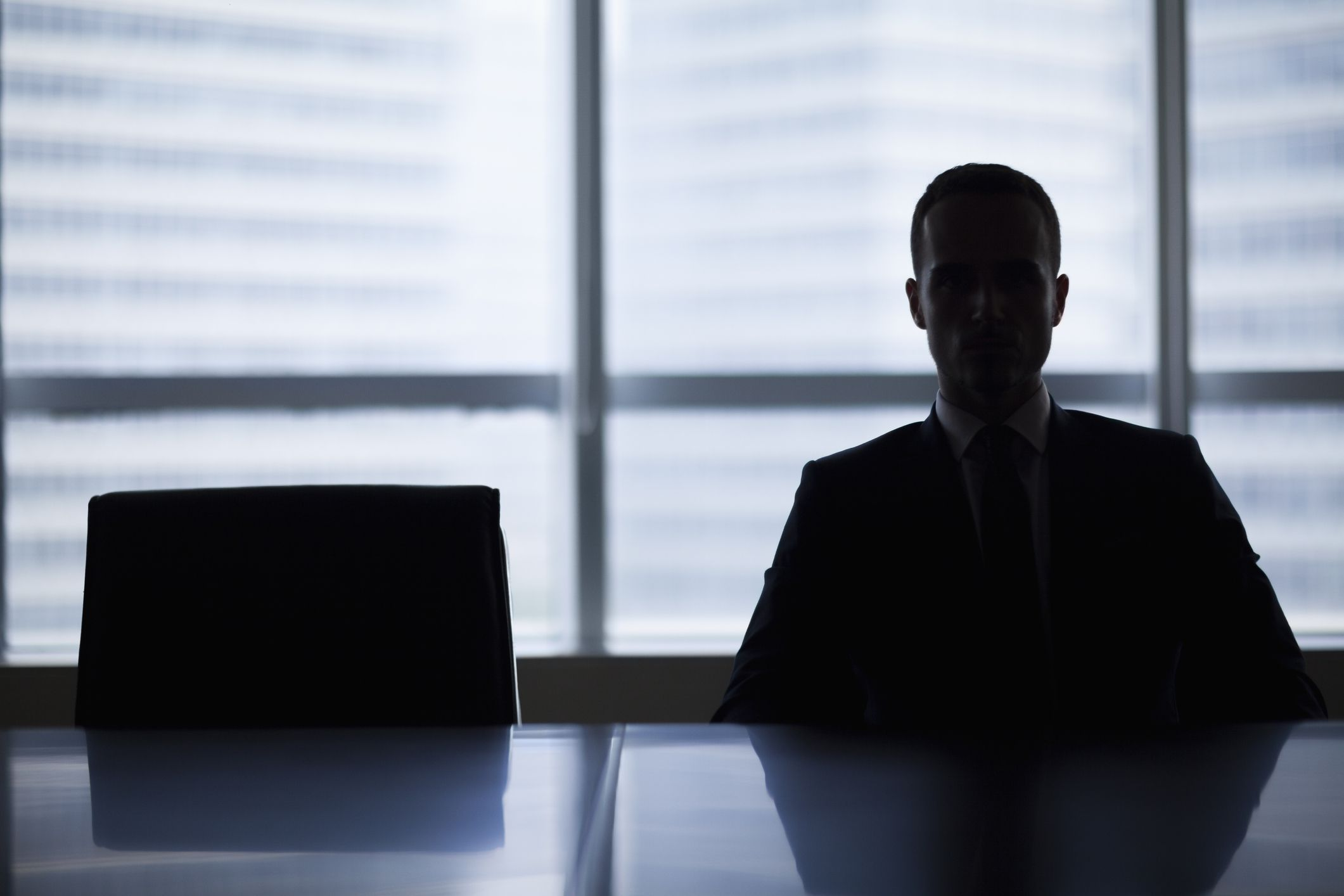 Man sitting in a boardroom with a unrecognizable face