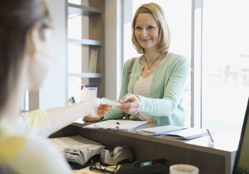 Receptionist taking patients insurance card in dentists office
