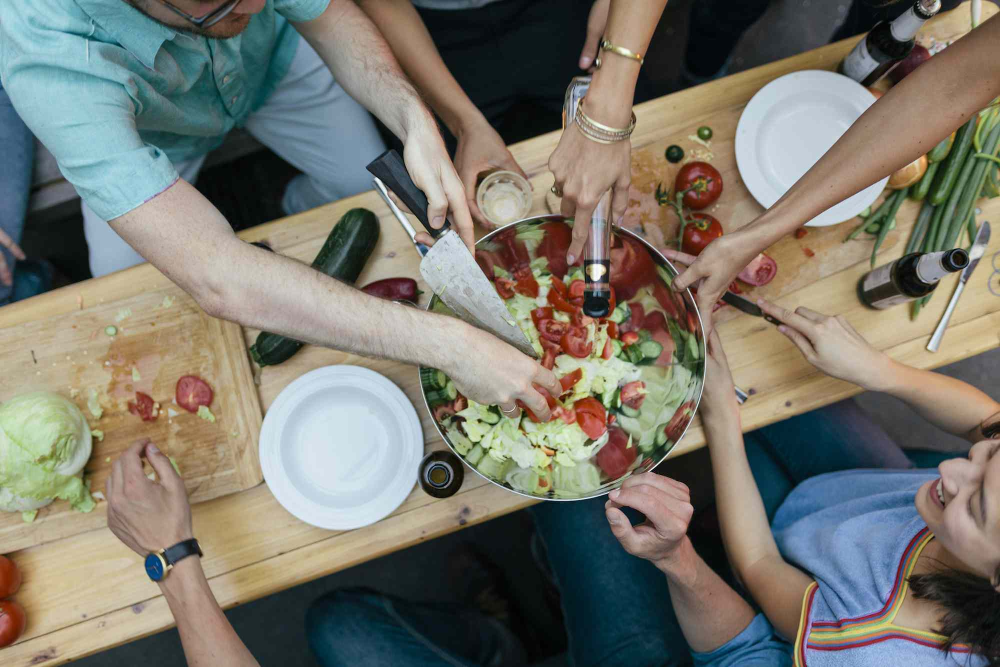 Multiple people gathered around a wooden table preparing a meal