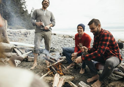 Barefoot friends enjoying beers by campfire on rugged beach