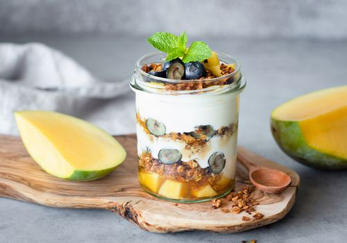 Breakfast yogurt parfait with granola, mango, berries in jar