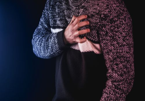 Close up of a person's chest wearing a sweater with a hand on their chest; their face is not visible and there is a slightly red hue overlaid.