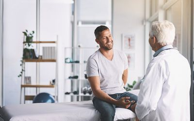 Young man in examining room with older male doctor
