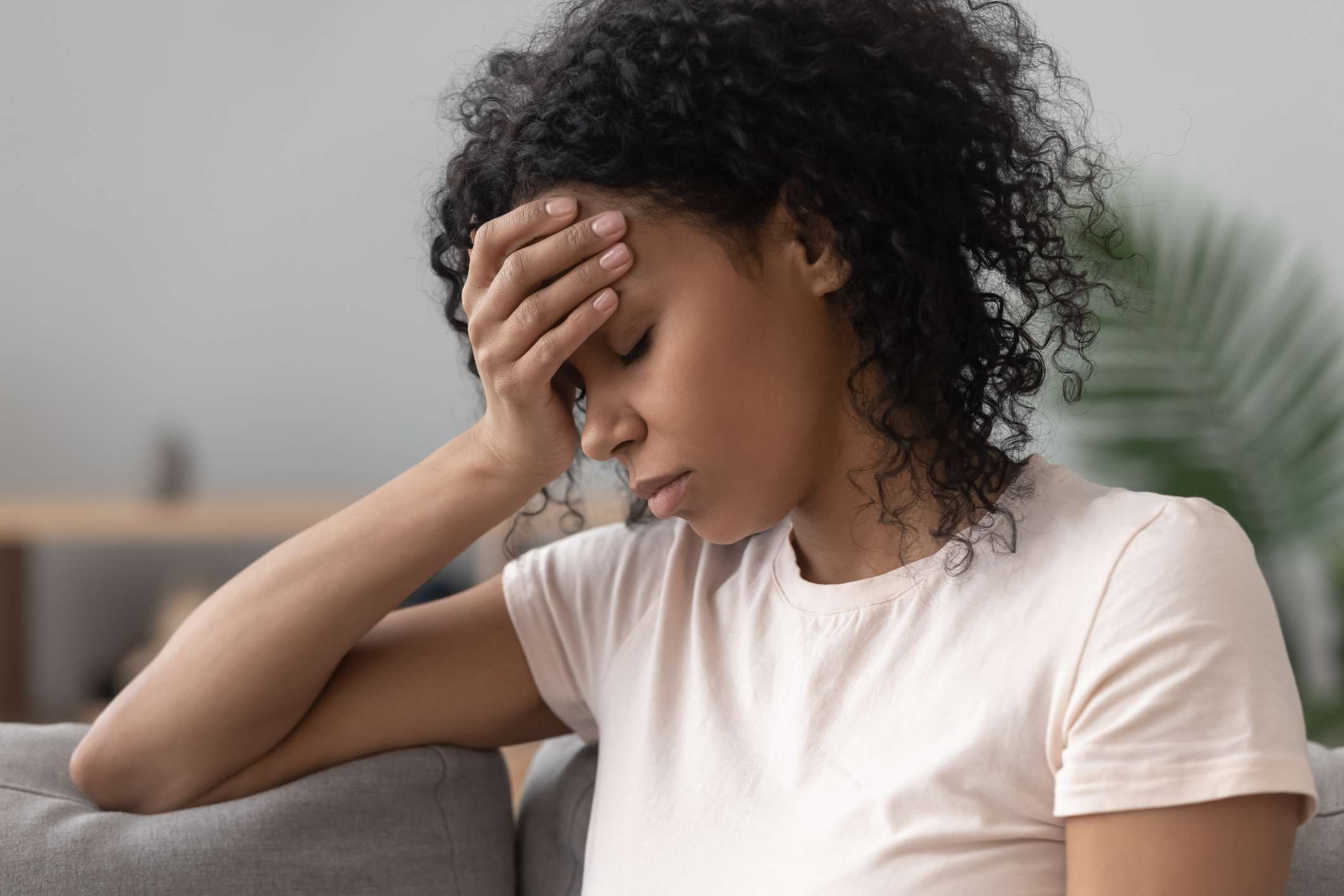 African woman sitting on couch feels unhappy having problems