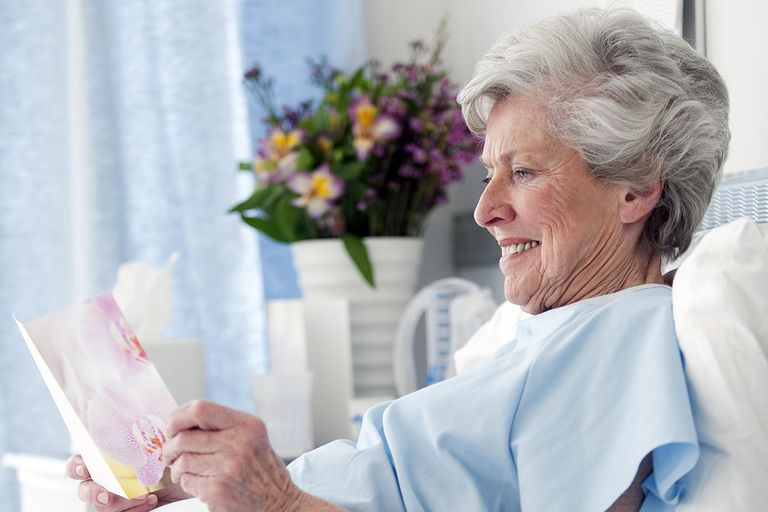 An Older Adult Recovering From Surgery, smiling and reading a card in a hospital bed