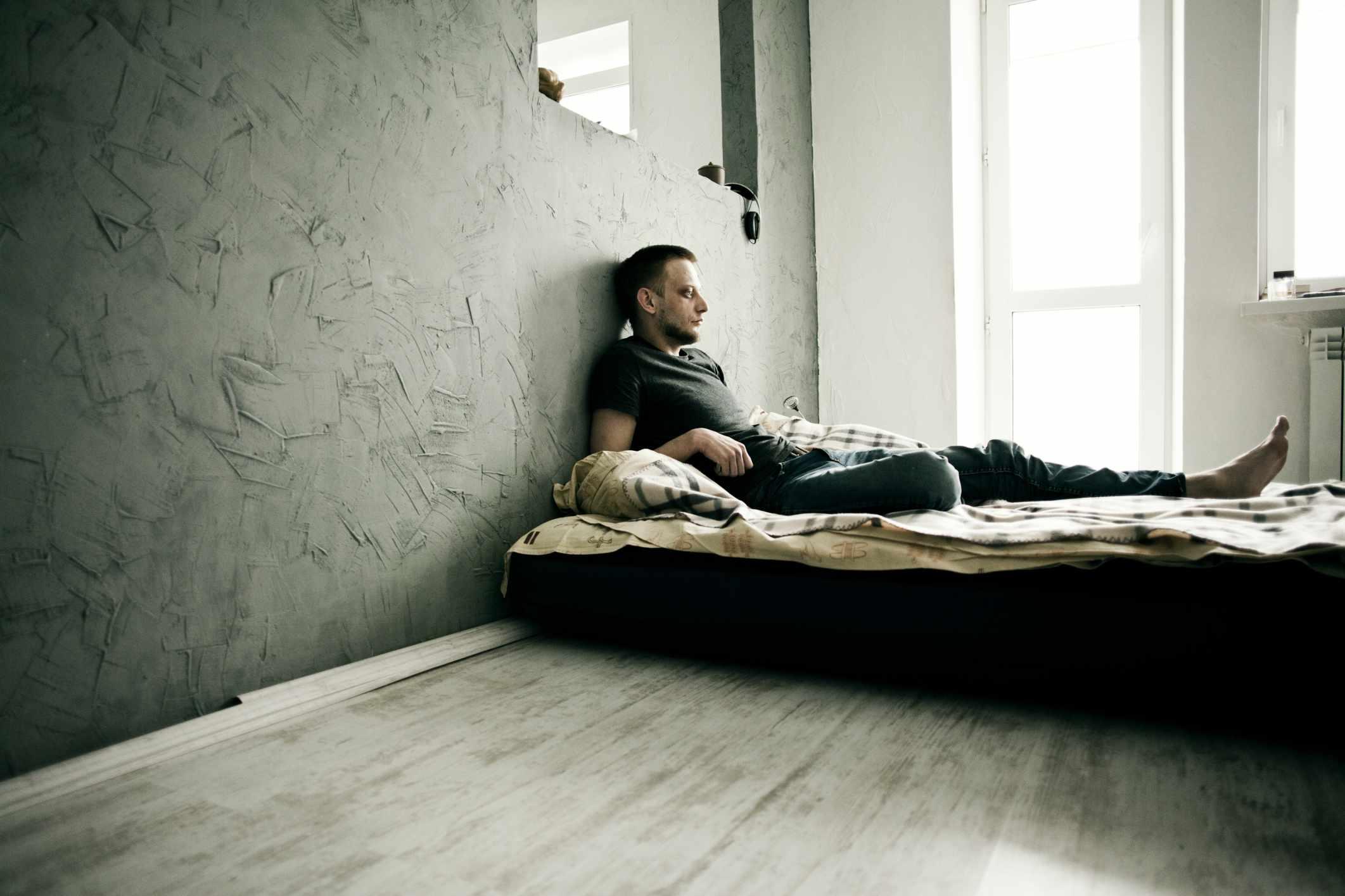 depressed man lying on bed in sparse room