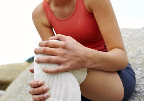 woman holding her knee in pain