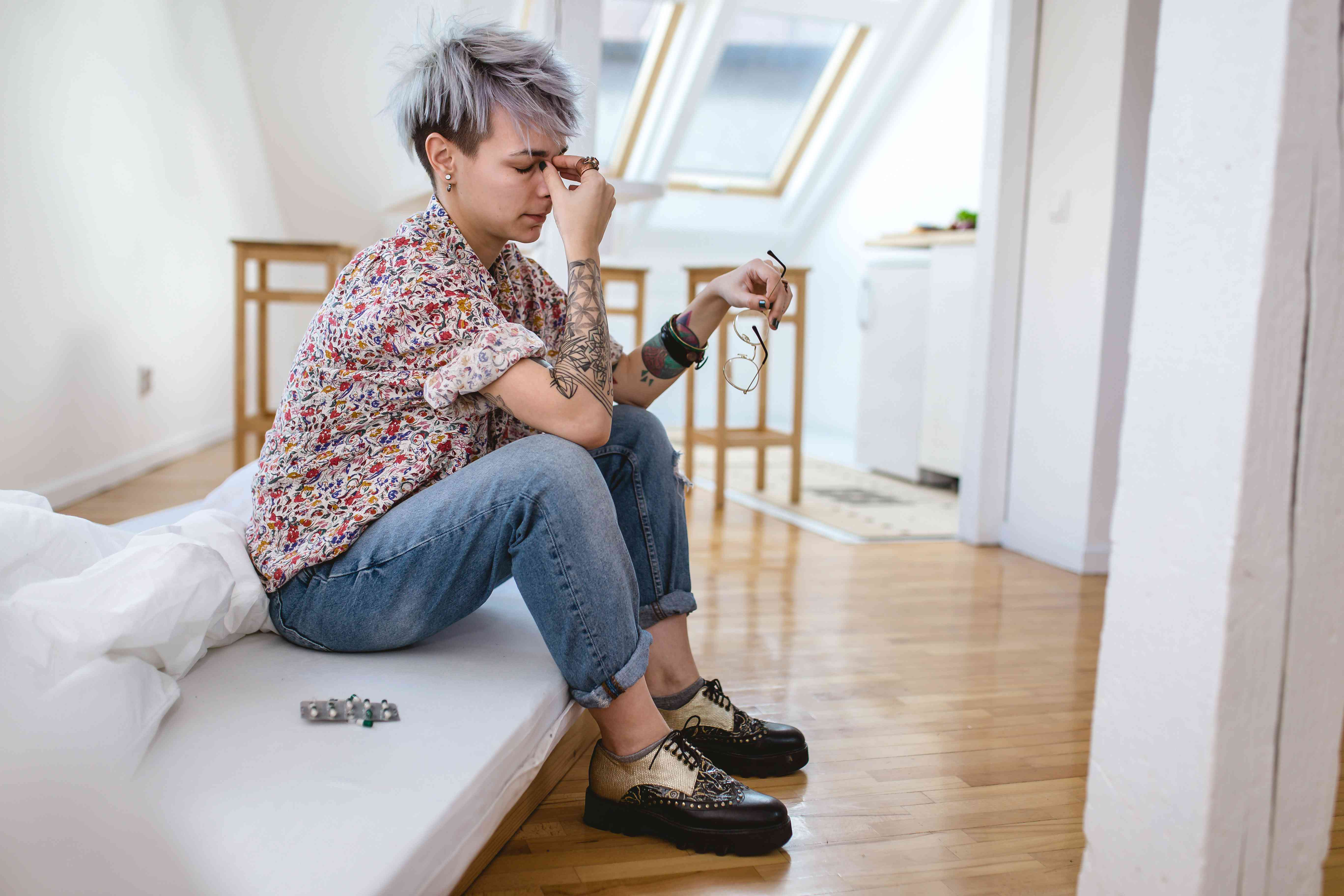 Girl sitting on bed in bad health