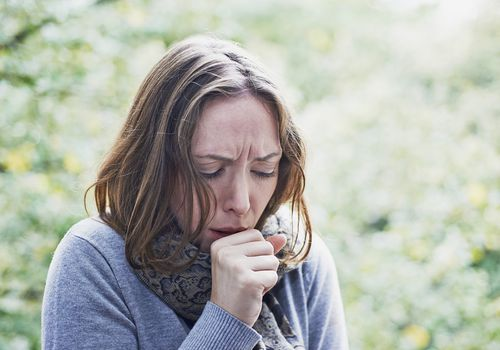 A woman coughing with her hand at her mouth