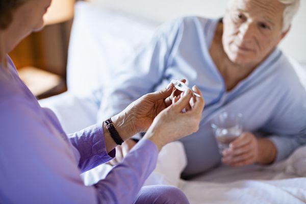 senior woman checking sick husband's temperature
