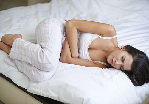 woman balled up on bed with cramps