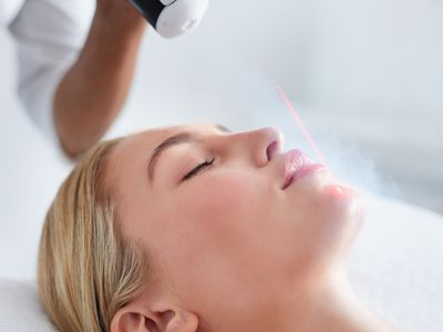 Young woman receiving local cryotherapy on her face