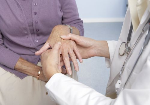 Older woman getting her hands looked at by a doctor