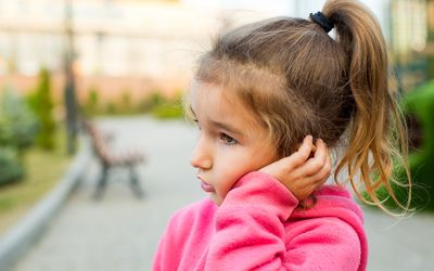 A Little Girl With A Sad And Frightened Face Holds Her Cheek With Her Hand