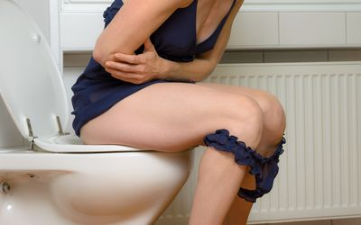 A constipated woman sitting on the toilet