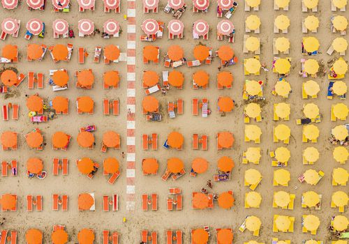 Overhead view of beach umbrellas grouped by color
