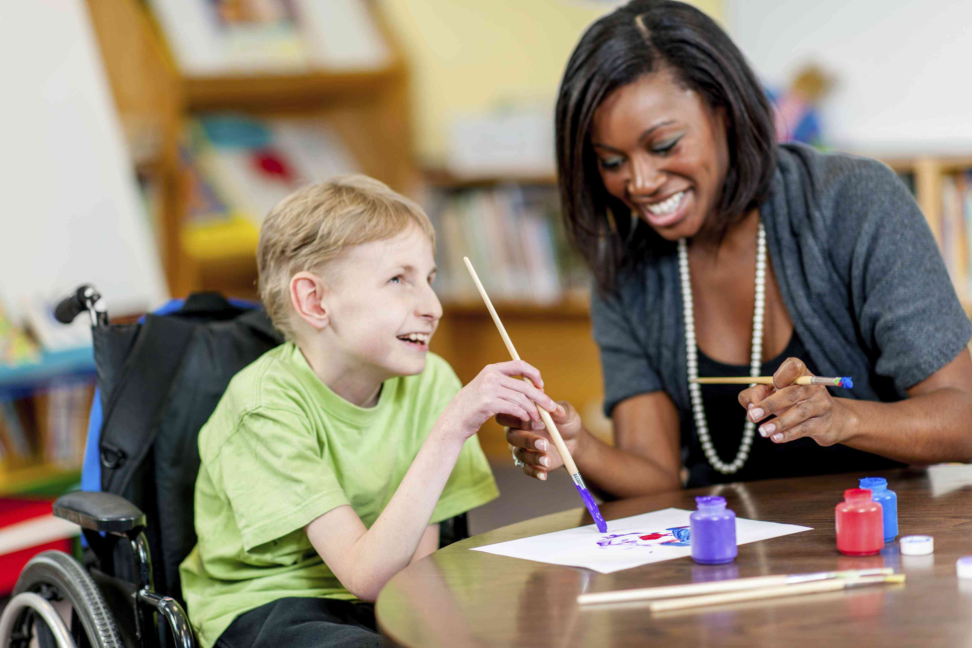 Special needs boy painting with help from an adult