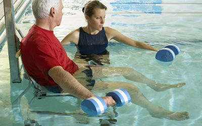 Photo of a man working in pool therapy with a young female coach.
