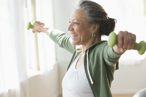 Compression of morbidity. Older woman lifting weights